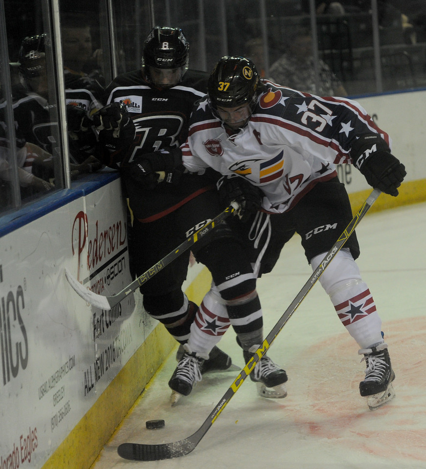 Chris Ciotti (8), left, forward for the Rapid City Rush, gets checked against the glass by Jordan Kwas (37), forward for the Colorado Eagles, in the first period on Wednesday, Oct. 28, 2015 in Loveland. (Photo by Trevor L Davis/Loveland Reporter-Herald)