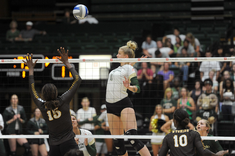 Reed Copeland (15), left, freshman at Wyoming, jumps to  respond to Colorado State's Acacia Andrews' (11), middle, spike on Tuesday, Oct. 13, 2015 in Fort Collins. (Photo by Trevor L Davis/Loveland Reporter-Herald)