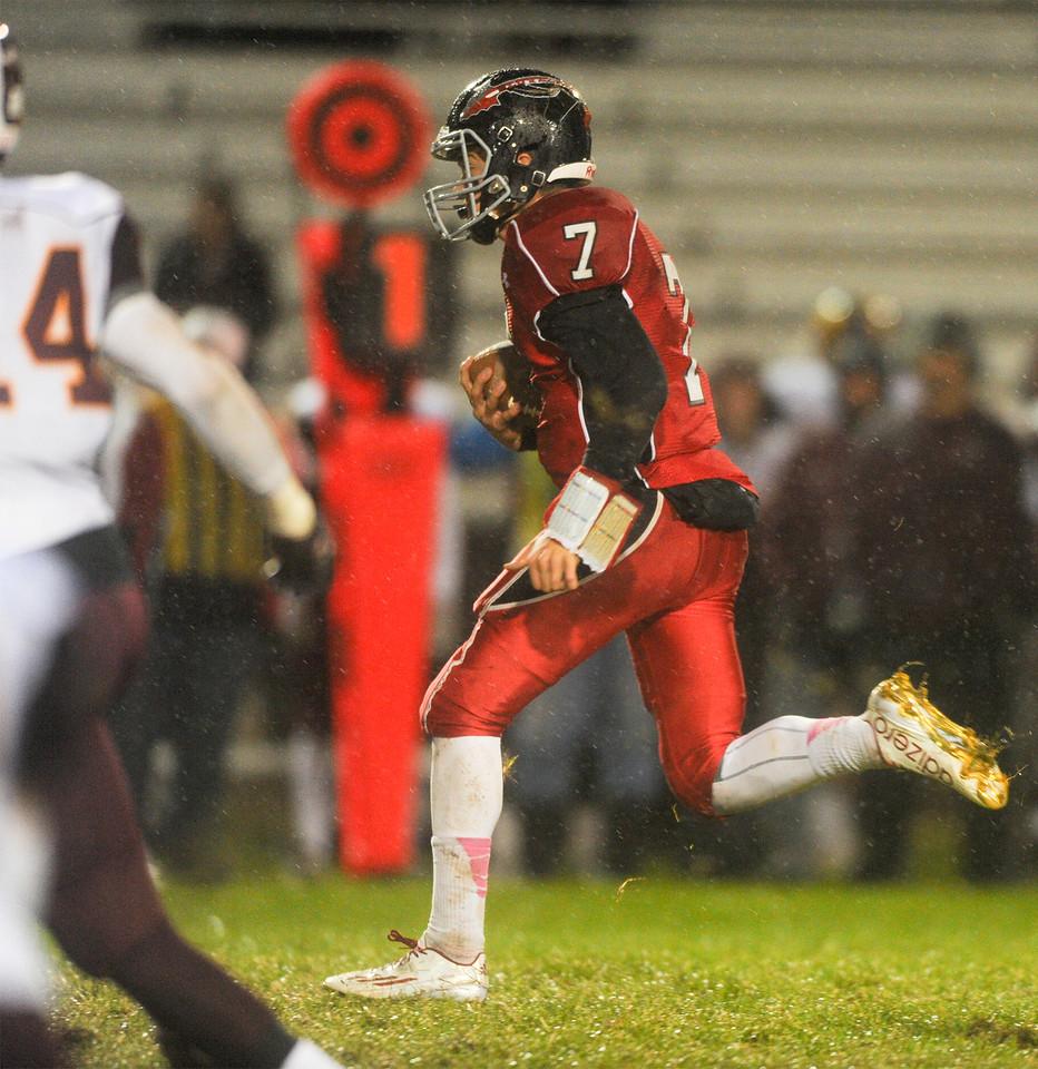 Ayden Eberhardt (7), quarterback for Loveland High, runs for a first down in the first half against Windsor on Thursday, Oct. 22, 2015 in Loveland. (Photo by Trevor L Davis/Loveland Reporter-Herald)