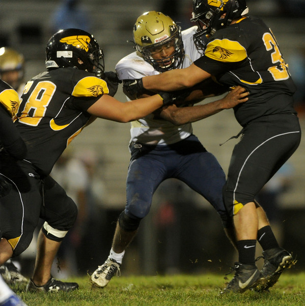 Tre'vaughn Gonzales (28), center, running back for Greeley West, tackled by Thompson Valley's Rhondy Martin (68), left, and Patton Graff (32), right, on Friday, Oct. 23, 2015 in Loveland. (Photo by Trevor L Davis/Loveland Reporter-Herald)
