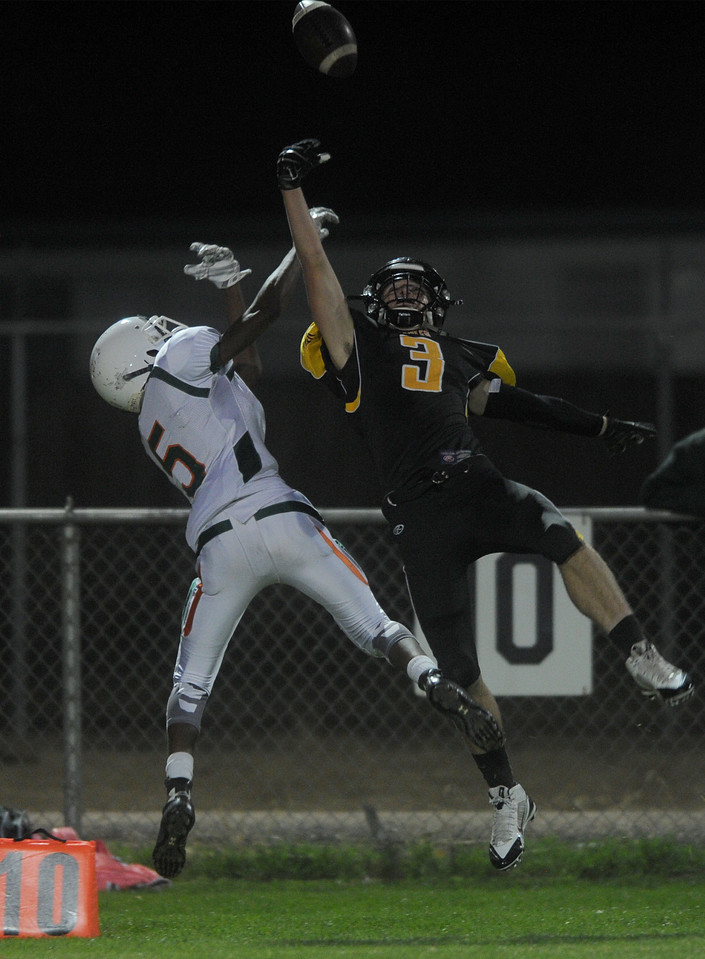 Jahvell Johnson-Humphries (5), wide receiver for Adams City, and Kevin Lutz (3), cornerback for Thompson Valley, jump for the ball in the fourth quarter on Friday, Oct. 9, 2015 in Loveland. (Photo by Trevor L Davis/Loveland Reporter-Herald)