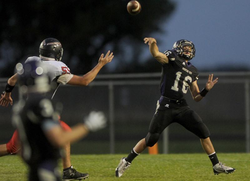 Dennis Landry, quarterback for Mountain View, gets rid of the ball under pressure on Friday, Sept. 18, 2015 in Loveland. (Photo by Trevor L Davis/Loveland Reporter-Herald)