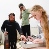 Master's students Ryan Parson and Paige Plier shows Freshman Kristina Samborski in the OUR Explorers Program how to collect water samples in Santa Rosa Sound Wednesday March 16, 2016 in Pensacola, Florida. (Michael Spooneybarger/ CREO)