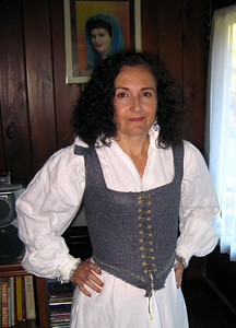 September 2010.  Bodice for a 16th C wool kirtle.  Wool, boned with 2mm round basket reeds, hand bound eyelets in yellow silk. Shoulders still not stitched at time of picture.  Time to stop complaining that none of my garb fits and make myself something new!