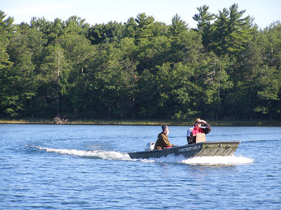 Gretchen Hansen (right) and Ali Mikulyuk (left) pilot a boat full of scuba gear to the far shore of the lake.