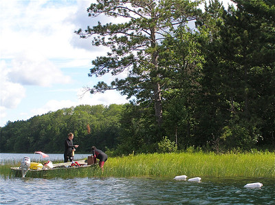 """After the """"support team"""" sets out a series of buoys marking transects, Gretchen and Ali prepare to head underwater and take a census of the macrophytes (aquatic plants) growing in Sparkling Lake."""