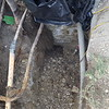 """We have to dig deep enough so that we can route our new electrical service under the concrete foundation. I believe we had to dig about 5' down. Anyways, there is a whole lot of """"what the heck"""" going on in this picture. The first is that very custom transition from large to small pipe. I wonder if using electrical tape to connect two pieces of conduit together was thought to be a good idea. Next, notice where the workers right foot is..."""