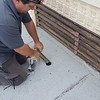 Here the consultant is using a coring tool to take core samples of all of the different roofs that I am sure were installed over the decades.  Many times, older rolled roofing material will contain asbestos.