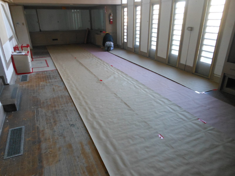 We will start our work in the Living Room, but before we start anything, we need to make sure that any potentially historic material is protected.  First, paper is being laid down and it will be followed by a thick layout board.