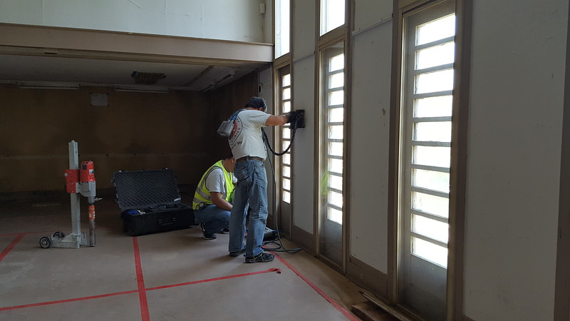 Work on the house has slowed as design work and testing continues. These workers are using ground penetrating radar to determine if the column/walls between each window is reinforced with steel.  We are using this method instead of boring holes in the wall, and possibly weakening it.  This information will affect the future structural design.
