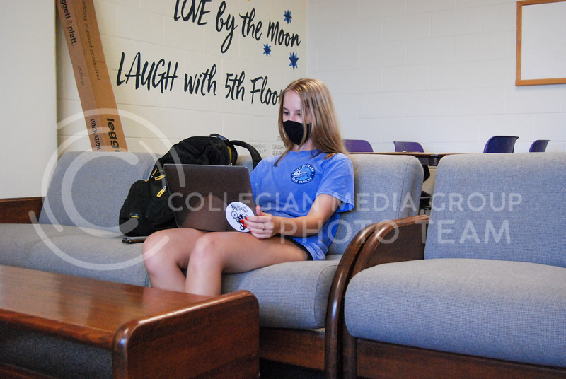 On the fifth floor couches, freshman Undecided major Sadie Brownfield wears her mask and works on assignments.<br /> Photo by Macey Franko