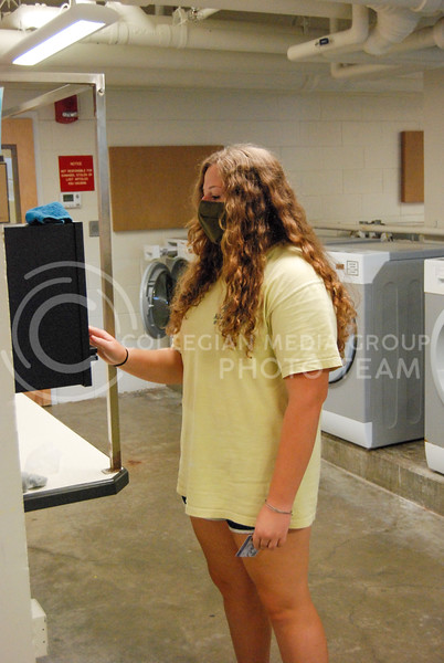 Beginning her laundry, sophomore Education major Hailey Shields swipes her ID to pay for and start the machines.<br /> Photo by Macey Franko