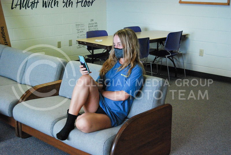 Lounging in the fifth-floor lobby of Ford Hall with her mask on, freshman Pre-Vet major Lauren Sanford plays on her phone.<br /> Photo by Macey Franko