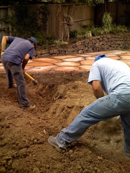 Clearing and preparing the soil deeply, below the new flagstone patio, for the upcoming lawn.