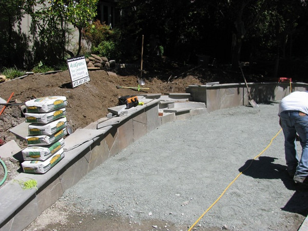 The flagstone facing is nearly done and the permeable base for the new brick parking area is prepared.