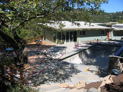 The pool and wooden deck are in and the flagstone patio is being built.