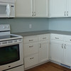 After - Kitchen Cabinets painted, walls painted, new countertops and wood floors installed