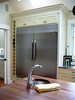 Beautifully built-in refrigerator with bottle storage alongside, skylights above