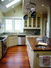 Note the tiger wood floors, cottage-look cabinets and butcher block island with prep sink