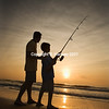 Man and young boy fishing in surf Man and young boy fishing in s