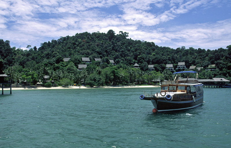Chinese Junk at anchor with hillside villas in the distance, Pangkor Laut Resort, an exclusive private island escape, Pangkor Laut, Selat Malaka (Straits of Malacca), Malaysia, Asia.