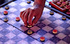 A man's hand moves a checker in a city streetside game in Pangkor, Palau Pangkor, Malaysia, Asia.