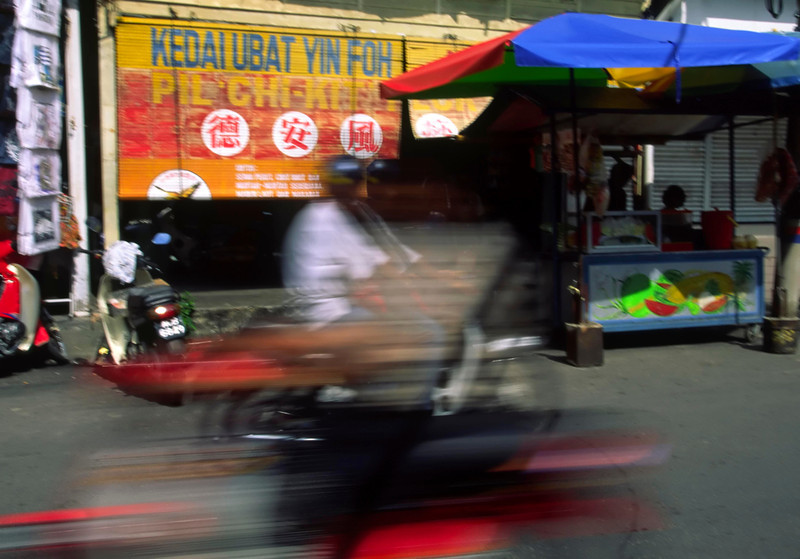 A moped races by in a blur in Pangkor, Palau Pangkor, Malaysia, Asia.