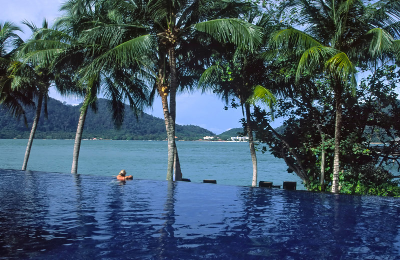 A guest luxuriates in the beautiful infinity pool at the exclusive private island Pangkor Laut Resort, Selat Malaka (Straits of Malacca), Malaysia, Aisa.