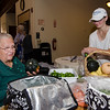 Mary Ann Guichard purchases vegetables from Annie Saball, of Brookside Family Farm, during the community resource fair at the Fitchburg Senior Center on Thursday evening. SENTINEL & ENTERPRISE / Ashley Green