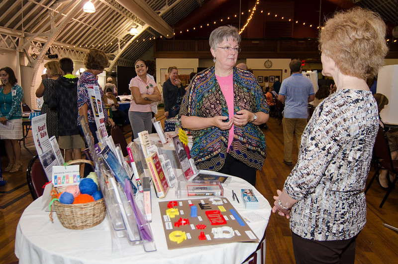 Librarian Sharon Bernard speaks with guests during the community resource fair at the Fitchburg Senior Center on Thursday evening. SENTINEL & ENTERPRISE / Ashley Green