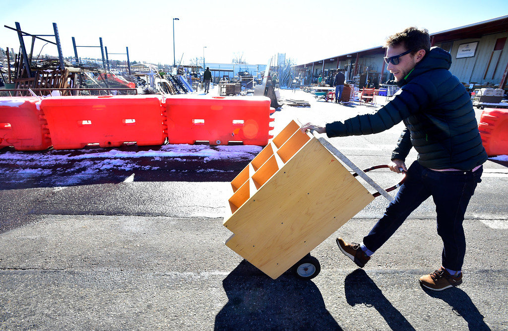 . BOULDER, CO - NOVEMBER 13, 2018  Ryan Fezler, who works at Neptune Mountaineering, carts away a cabinet he found at Resource Materials Reuse & Tool Library facility on Arapahoe Road on Tuesday morning.  Workers from the store are renovating an employees\' bathroom at their shop. For more photos go to dailycamera.com.  (Photo by Paul Aiken/Staff Photographer)