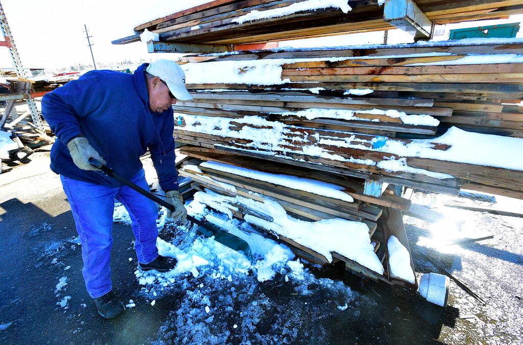 . BOULDER, CO - NOVEMBER 13, 2018  Abel Portillo works to clean off the lumber area after a recent snow at the Resource Materials Reuse & Tool Library facility on Arapahoe Road on Tuesday morning. One of the plans for the facility is more roofing to protect the materials from the elements. For more photos go to dailycamera.com.  (Photo by Paul Aiken/Staff Photographer)