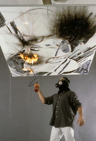 Burning/scorching surface of canvas with a torch, slide 2.  Afterwards, the burned and smoky plane is sealed with clear emulsion.