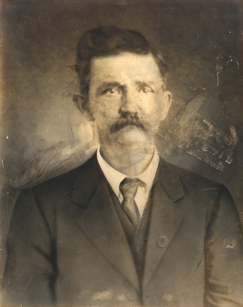Large portrait of man in Missouri - before.<br /> This had been displayed and stored in a wooden frame with no glass or other protection and had been damaged. It appeared that something wet came in contact with it and there had been an attempt to wipe it off, which ruined some of the emulsion of the photograph. It also had multiple scratches and small areas with the emulsion missing. It appears to be a slightly fuzzy photograph of a photograph with some finer details in the clothing added by hand.