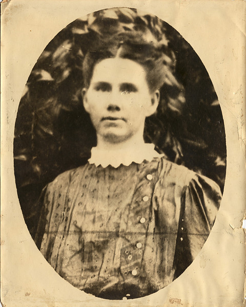 Large portrait of woman in Missouri. As with the man's photograph, this one had been unprotected in a simple frame for many years. As a result it suffered physical damage to the print including punctures just under the eye. It also seems to be a photograph of a photograph without sharp detail. There is a dark line and a dark smudge on the front of her dress which may have been on the original photograph. Restoration included removing these, repairing the damage under the eye, and deleting small dust and scratches.