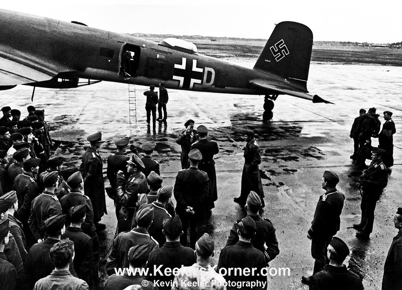 Focke Wulf 200 Condor.<br /> <br /> This photo depicts the Focke Wulf 200 Condor in the background as an unknown Luftwaffe officer is being saluted as he arrives at an airfield.<br /> <br /> This is a restoration of an original photo. Details regarding location date and personnel are unknown.<br />  <br /> Photo displayed and reproduced with the permission of the owner.