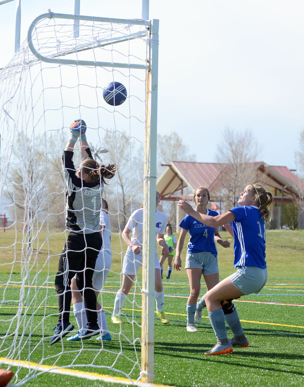 . Resurrection Christian\'s Ella Peacock (18)  and Jenni Pronozuk watch as a corner kick slips through the hands of Estes Park goalie Kyra MacGregor during Thursday\'s Patriot League game at Loveland Sports Park. (Mike Brohard/Loveland Reporter-Herald)