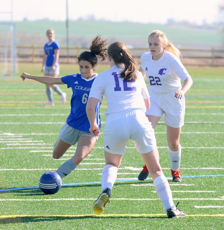 . Resurrection Christian\'s Olivia Mascio loads up to take a shot as Estes Park\'s Sage Shumate (12) closes in during Thursday\'s Patriot League game at Loveland Sports Park. (Mike Brohard/Loveland Reporter-Herald)