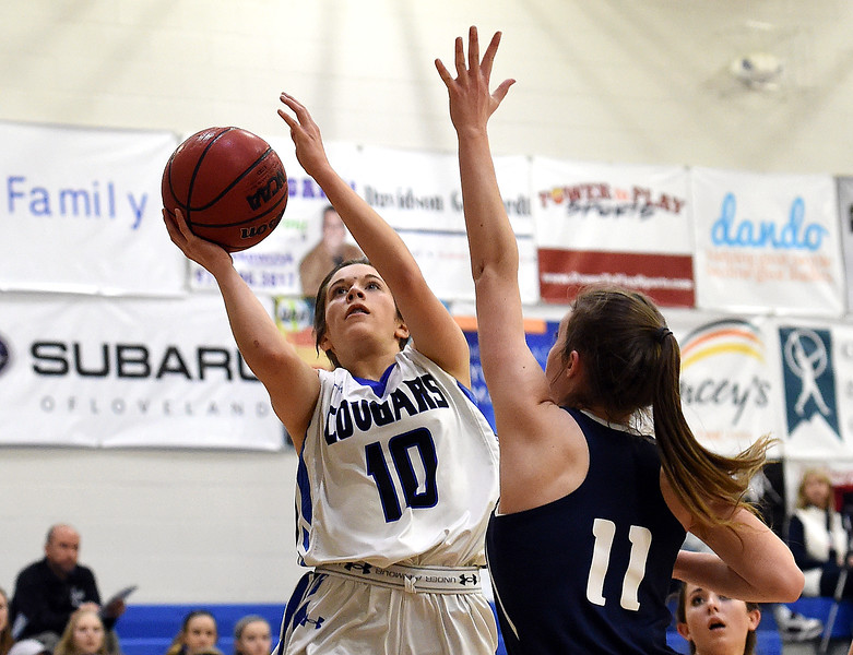 Resurrection Christian's (10) Juju Hemeyer goes up for a shot past Liberty Commons' (11) Eve Norman during their game Thursday, Jan. 18, 2018, at Resurrection Christian School in Loveland. (Photo by Jenny Sparks/Loveland Reporter-Herald)