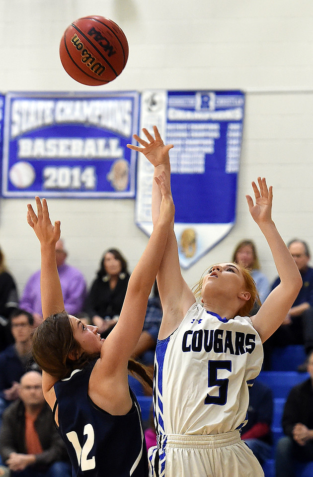 Resurrection Christian's (5) Katelyn Anderson goes up for a shot past Liberty Commons' (12) Samantha Tsiouvaras during their game Thursday, Jan. 18, 2018, at Resurrection Christian School in Loveland. (Photo by Jenny Sparks/Loveland Reporter-Herald)