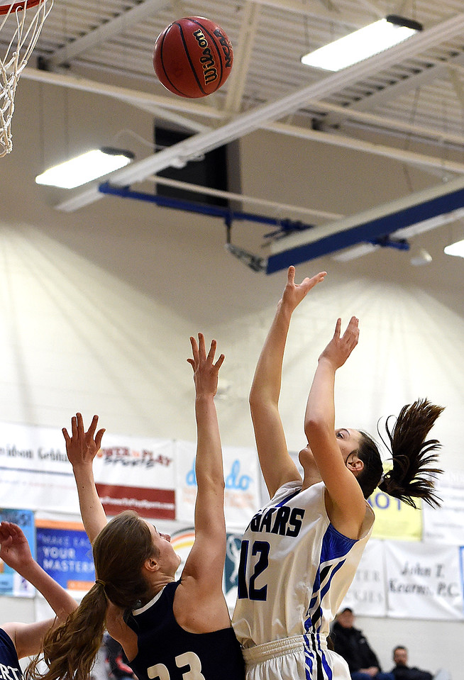 Resurrection Christian's (12) Kaari Ausenhus goes up for a shot past Liberty Commons' (33) Anne Dutton during their game Thursday, Jan. 18, 2018, at Resurrection Christian School in Loveland. (Photo by Jenny Sparks/Loveland Reporter-Herald)