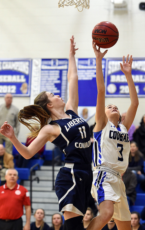 Resurrection Christian's (3) Gracie Stults goes up for a shot past Liberty Commons' (11) Eve Norman during their game Thursday, Jan. 18, 2018, at Resurrection Christian School in Loveland. (Photo by Jenny Sparks/Loveland Reporter-Herald)