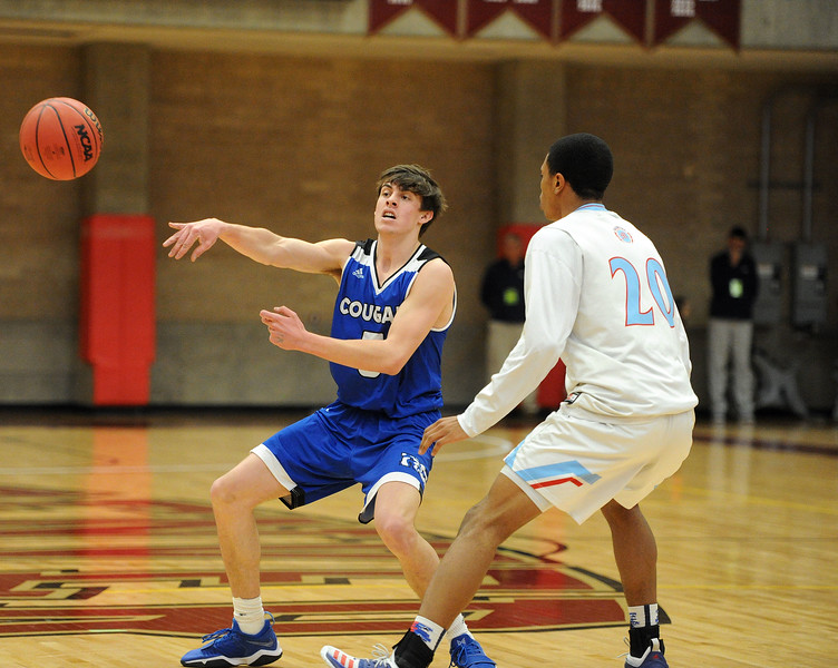 Reece Johnson dishes a pass during Resurrection Christian's Great 8 game against Manual at Magness Arena on Thursday, March 7. (Colin Barnard/Loveland Reporter-Herald)