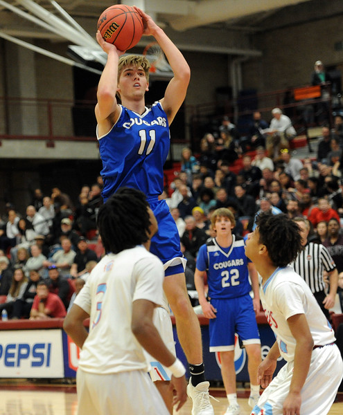 Reade Lindgren rises above two defenders for a jumper during Resurrection Christian's Great 8 game against Manual at Magness Arena on Thursday, March 7. (Colin Barnard/Loveland Reporter-Herald)
