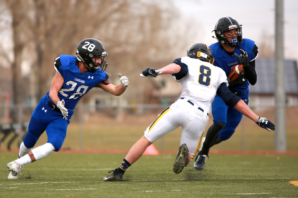 . Resurrection Christian�s (1) Colton Stahla catches the ball next to teammate (28) Trenton Brand as Rifle�s (8) Levi Warfel plays defense in the 2A state playoffs at Windsor High School on Saturday, Nov. 10, 2018 in Windsor, Colo.Photo by Taelyn Livingston/ Loveland Reporter-Herald