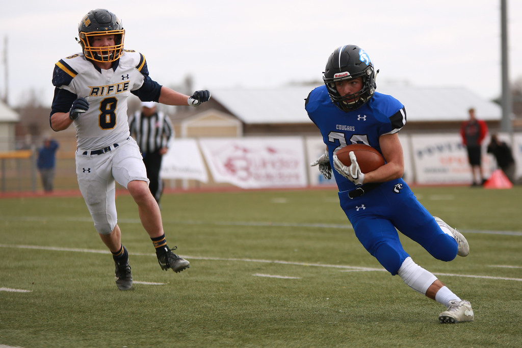 . Resurrection Christian�s (28) runs with the ball as Rifle�s (8) Levi Warfel is close behind in the 2A state playoffs at Windsor High School on Saturday, Nov. 10, 2018 in Windsor, Colo.