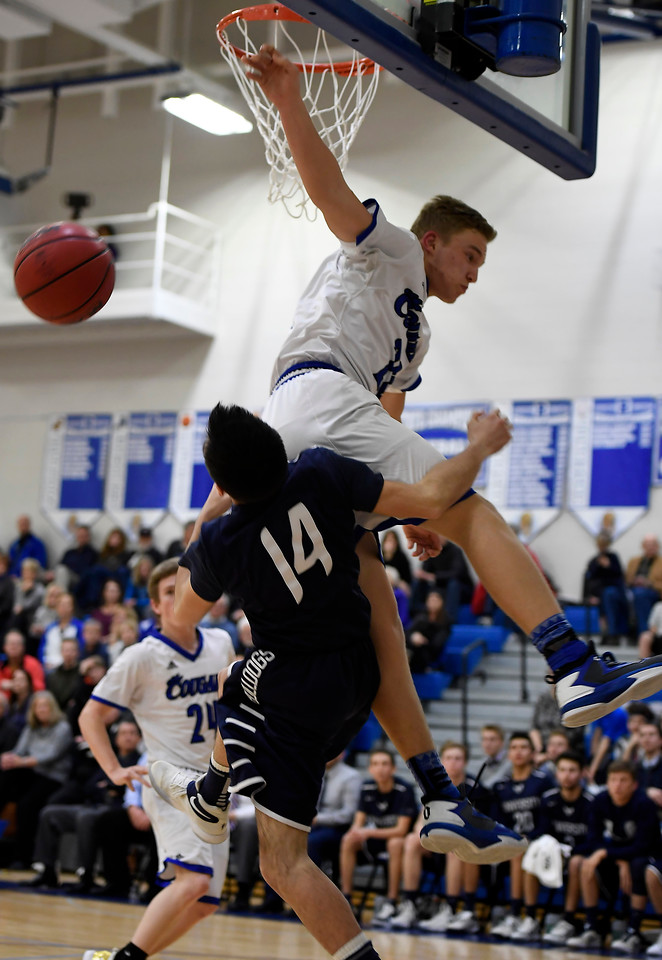 Resurrection's #20 Zane Zuhlke makes a shot as University's #14 Nate Martinez tries to intercept during the game on Thursday, February 23, 2017 at Resurrection High School, Loveland.