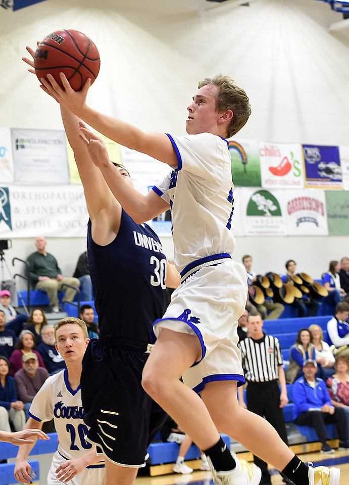 Resurrection Christian's #24 Mike Stevenson goes up for a shot as University's #30 Barry Holgerson during their game Tuesday, Feb. 7, 2017, at Resurrection Christan School in Loveland. (Photo by Jenny Sparks/Loveland Reporter-Herald)<br /> 24