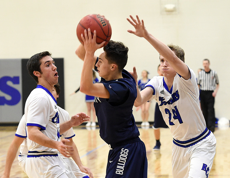 Resurrection Christian's #11 Conner Stahla, left, and #24 Mike Stevenson try to block University's #1 Izak Natividad during their game Tuesday, Feb. 7, 2017, at Resurrection Christan School in Loveland. (Photo by Jenny Sparks/Loveland Reporter-Herald)<br /> 24, 11 u1