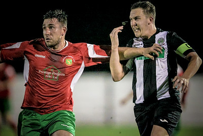 Paul Beesley holds off the Retford United captain as he runs into the penalty box.